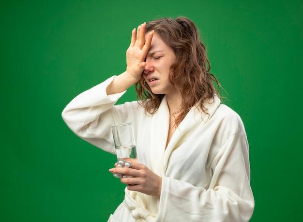 Schwaches junges krankes mädchen mit geschlossenen augen, das weißes gewand hält, das glas wasser hält, das hand auf stirn lokalisiert auf grün hält
