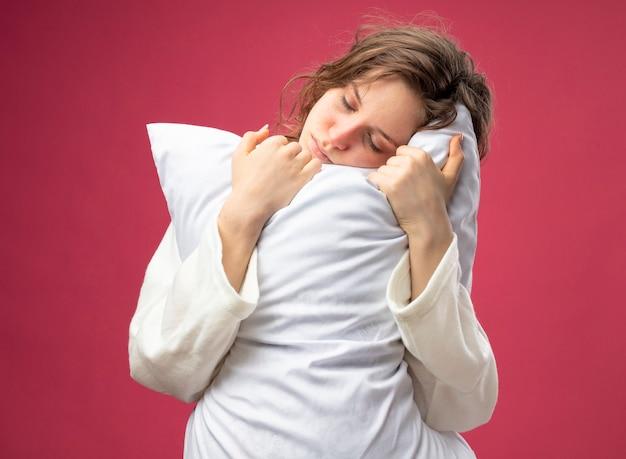 Schwaches junges krankes mädchen mit geschlossenen augen, die weißes gewand umarmten kissen lokalisiert auf rosa tragen
