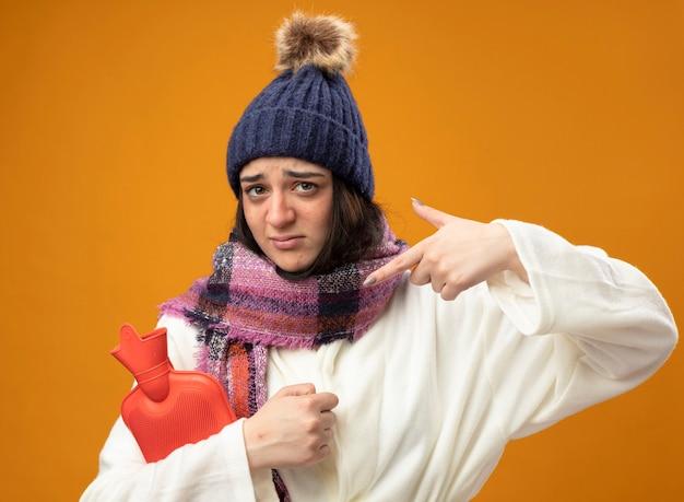Schwaches und trauriges junges kaukasisches krankes mädchen, das robe wintermütze und schal hält und auf heißwassersack zeigt, der auf orange wand lokalisiert ist