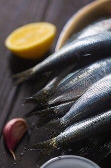 Schwänze von fangfrischen frischen sardinen mit zitrone auf dem tisch