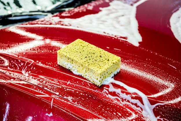 Schwamm über dem roten auto zum waschen.