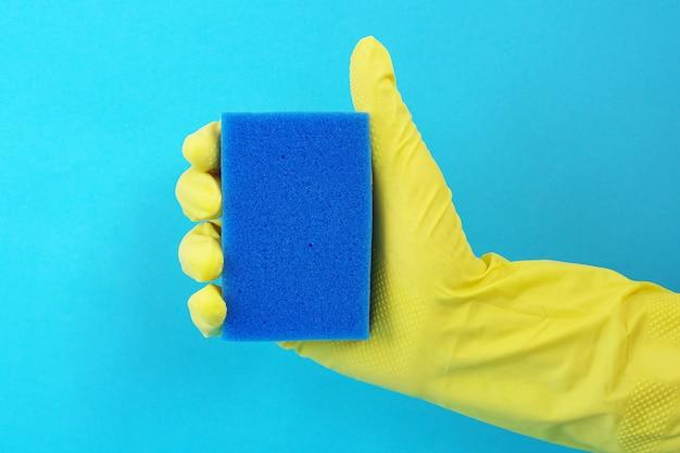 Schwamm zum geschirr spülen in der hand in einem gelben gummihandschuh