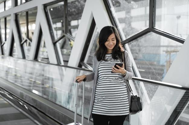 Schwangere asiatische frauen sehen handys, wenn sie durch die rolltreppe gehen