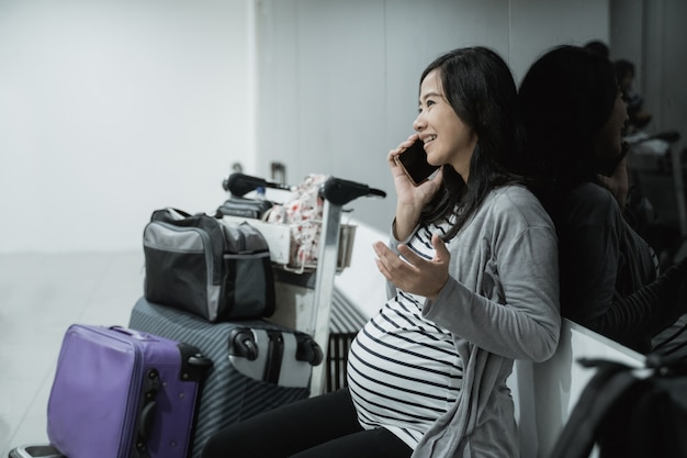Schwangere asiatische frauen telefonieren mit smartphones