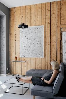 Schwangere blonde frau entspannt sich auf einem grauen sofa