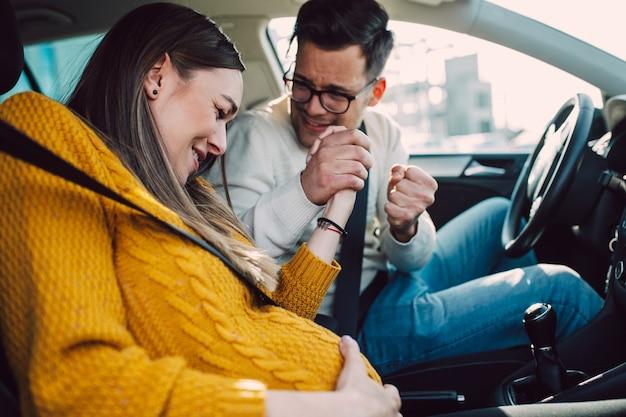 Schwangere, die beginnen, schmerzen und kontraktionen zu spüren, während ihr besorgter ehemann ein auto fährt.