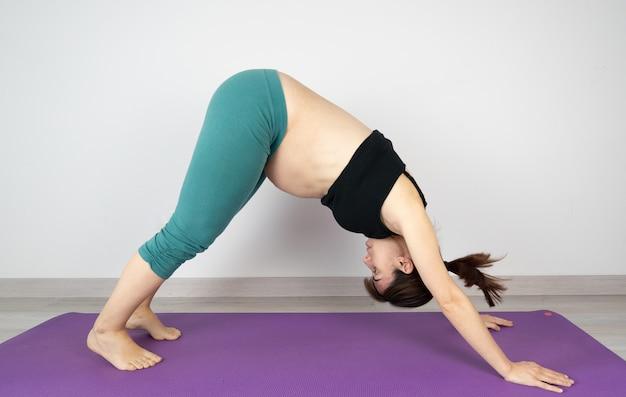 Schwangere, die yoga-stellungen auf einer matte tut. adho mukha svanasana