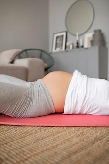 Schwangere, die zu hause yoga macht