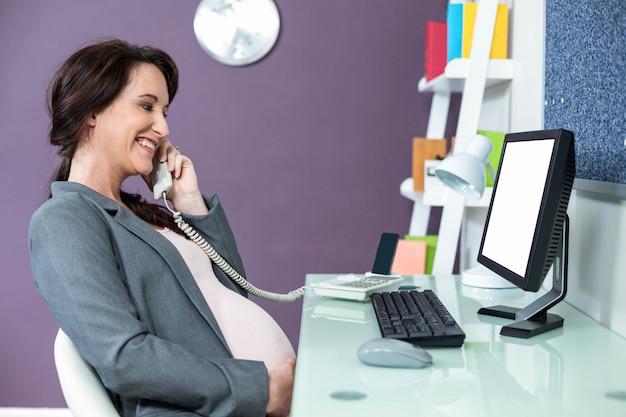 Schwangere frau am telefon im büro