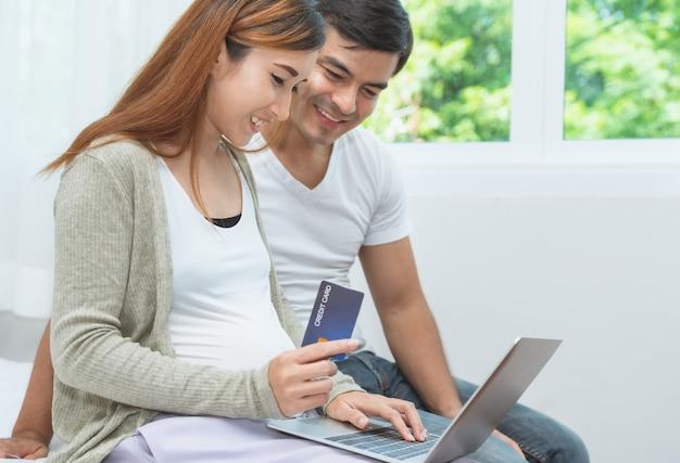 Schwangere frau asain und ihr ehemann, die online auf laptop-computer und zahlung mit kreditkarte zu hause kauft
