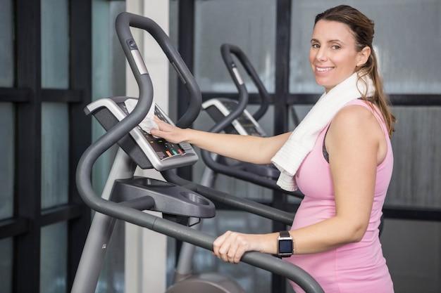 Schwangere frau auf crosstrainer in der turnhalle