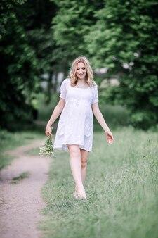 Schwangere frau auf einem spaziergang an einem sommertag.