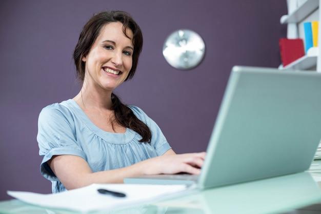 Schwangere frau auf ihrem laptop zu hause