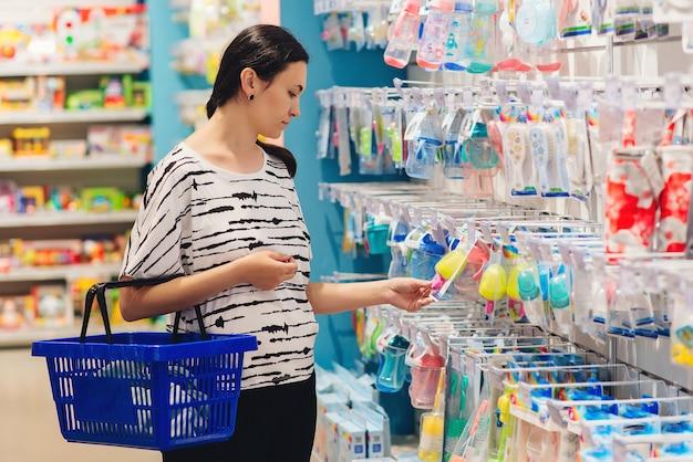 Schwangere frau beim einkaufen im babyladen. frau, die babysachen im babyshop wählt.
