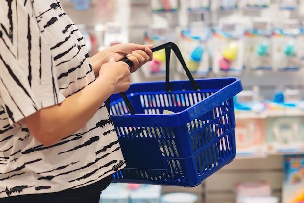 Schwangere frau beim einkaufen im babyladen. mama wählt neugeborenes babyprodukt im supermarkt