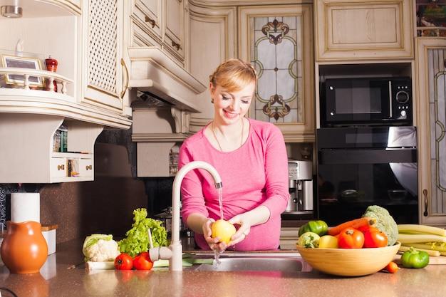 Schwangere frau bereitete ein abendessen in der küche vor. konzept für gesunde ernährung