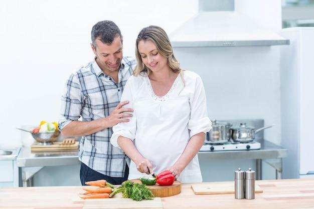 Schwangere frau beschäftigt im küchenausschnittgemüse