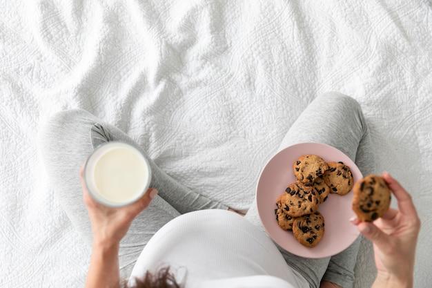 Schwangere frau der draufsicht, die schokoladenplätzchen isst
