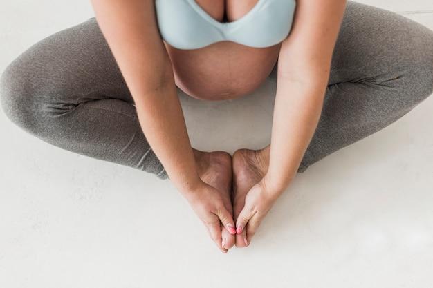 Schwangere frau der draufsicht, die übungen tut