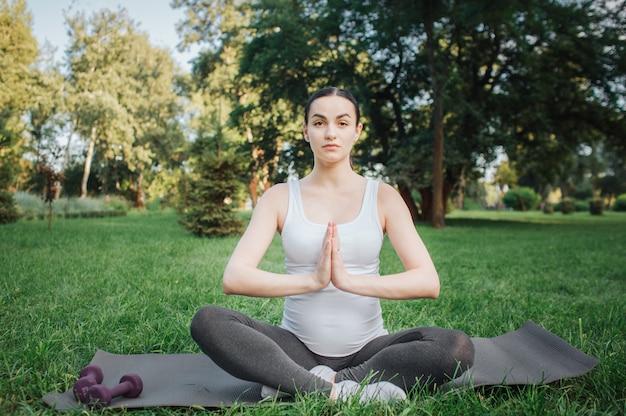 Schwangere frau der junge, die draußen meditiert. sie sitzt auf yoga-kumpel in lotus-pose. modell halten hände in betender position.