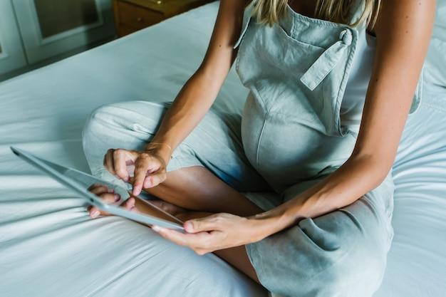 Schwangere frau der junge, die eine digitale tablette beim auf bett zu hause stillstehen verwendet