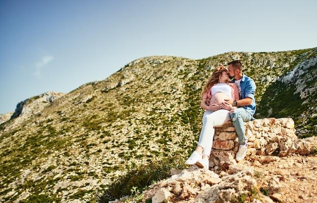 Schwangere frau der junge, die mit ihrem ehemann in den bergen geht