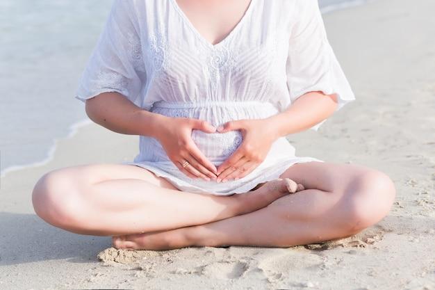 Schwangere frau der junge, die yogaübungen auf dem strand tut