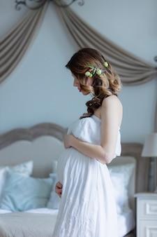 Schwangere frau der junge im weißen kleid