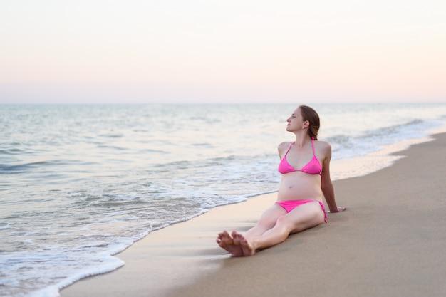 Schwangere frau der junge sitzt auf dem seeufer und genießt natur. einsamer strand, zeit vor sonnenuntergang
