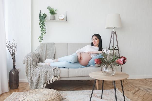 Schwangere frau der junge zuhause. nahaufnahmeporträt der frau erwartend. schöne frau, die auf ihre kleine babygeburt wartet.