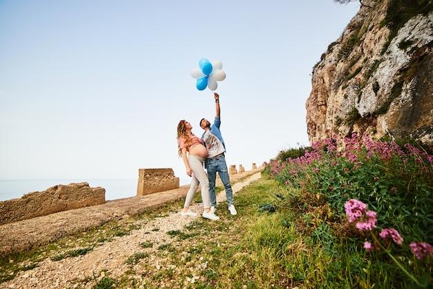 Schwangere frau der jungen gesunden schönheit mit ihrem ehemann und ballonen draußen