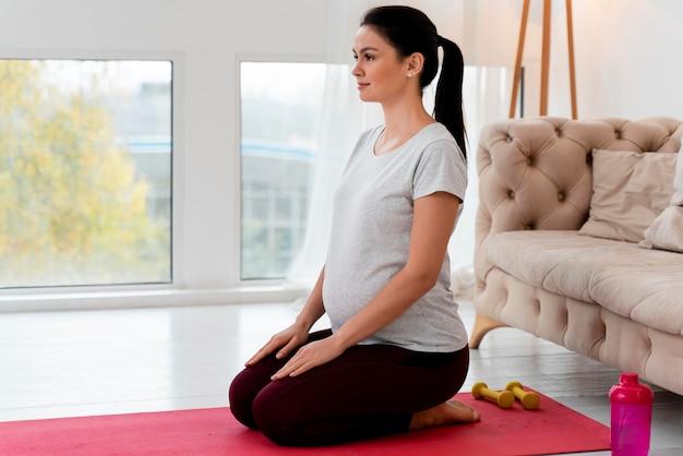 Schwangere frau der seitenansicht, die yoga tut