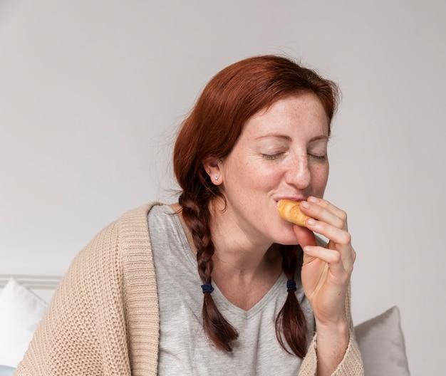 Schwangere frau der vorderansicht, die croissant genießt