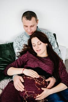 Schwangere frau, deren bauch mit glühwürmchen geschmückt ist, umarmt ihn. fröhliche weihnachten. weihnachten dekoriertes interieur. schwangerschaft, familienurlaub, menschen- und erwartungskonzept.