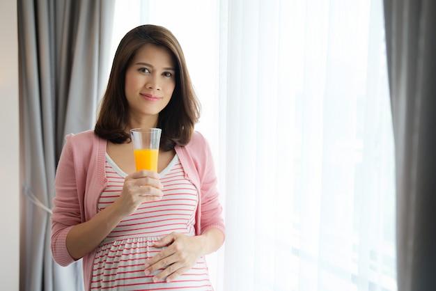 Schwangere frau des asiaten, die glas orangensaft hält.