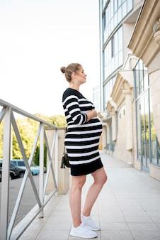 Schwangere frau des vollen schusses, die draußen steht
