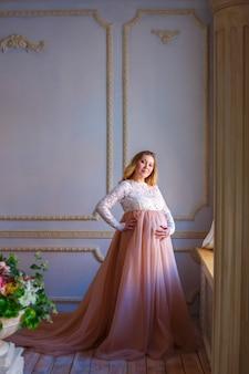 Schwangere frau, die am fenster, in einem schönen kleid, mutterschaft wartet