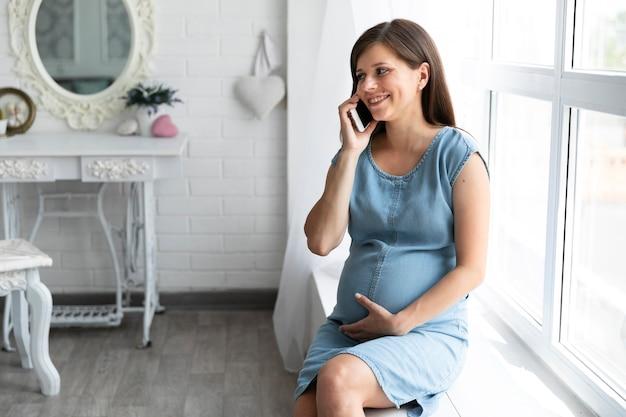 Schwangere frau, die am telefon spricht