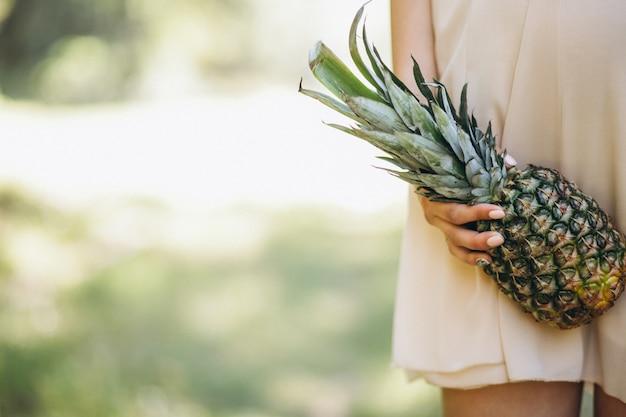Schwangere frau, die ananas hält
