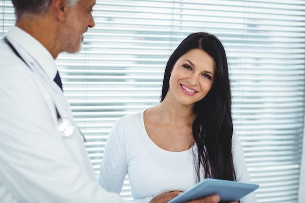 Schwangere frau, die auf doktor in der klinik einwirkt