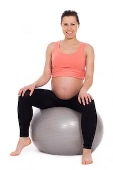 Schwangere frau, die auf einer kugel sitzt