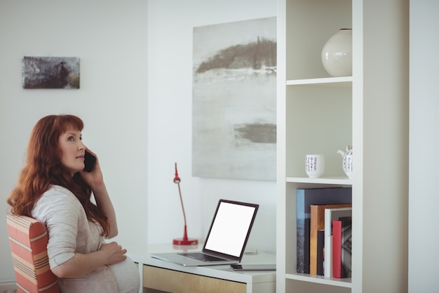 Schwangere frau, die auf handy im arbeitszimmer spricht