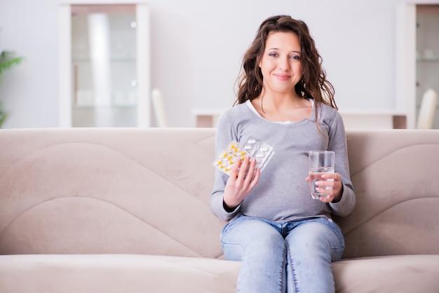 Schwangere frau, die auf sofa sitzt