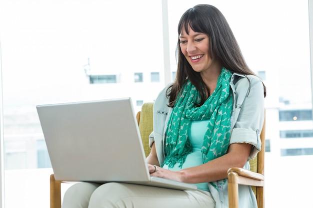 Schwangere frau, die auf stuhl sitzt und zu hause laptop verwendet