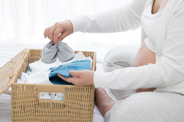 Schwangere frau, die babyprodukte vor pränatal vorbereitet und plant