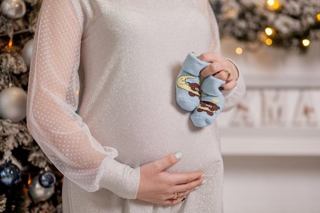 Schwangere frau, die babyschuhe nahe ihrem bauch hält
