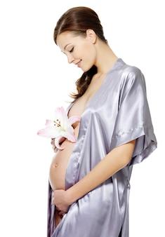 Schwangere frau, die bauch und blume lokalisiert auf weiß hält