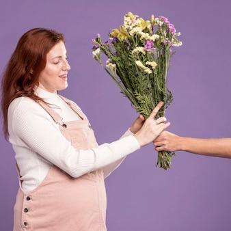 Schwangere frau, die blumenstrauß erhält
