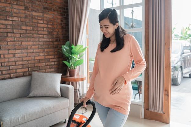 Schwangere frau, die boden mit staubsauger reinigt