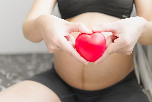 Schwangere frau, die das kleine herzspielzeug zu hause sich entspannt im schlafzimmer hält.